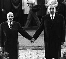 Helmut Kohl and François Mitterrand holding hands in the Douaumont cemetery, Verdun, in 1984.