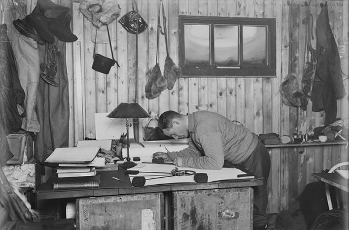 Terra Nova expedition: Teddy Evans working on a map in the hut at Cape Evans.