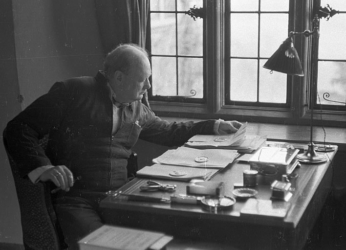Churchill in his siren-suit at his desk in his country home Chartwell in 1939.