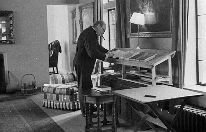 Churchill in his siren-suit at his standing-desk in his country home Chartwell in 1939.